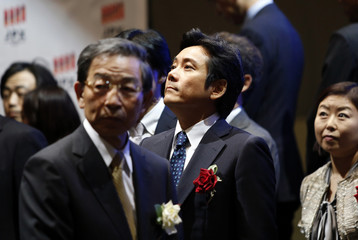 Recruit Holdings President and CEO Minegishi looks at the company's stock price on the bourse at the Tokyo Stock Exchange after a ceremony to mark the company's debut on the TSE in Tokyo