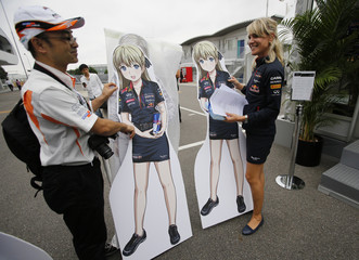 A Japanese fan presents a Manga inspired standee of the Red Bull hospitality crew to Britta Roeske, press officer of Red Bull Formula One driver Sebastian Vettel of Germany, at the Suzuka circuit in Suzuka