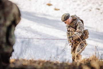 Instructor helping another soldier to climb up the hill. People and military concept