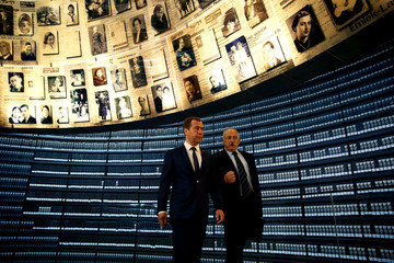 Russian Prime Minister Dmitry Medvedev looks at pictures of Jews killed in the Holocaust during a visit to the Hall of Names at Yad Vashem's Holocaust History Museum in Jerusalem
