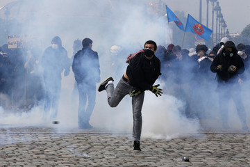 Masked youths face off with French police and gendarmes during a demonstration in Paris as part of nationwide protests against plans to reform French labour laws
