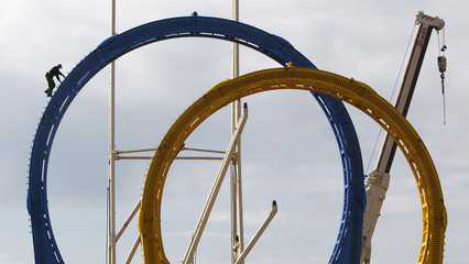 Worker climbs up roller coaster in preparation for Oktoberfest in Munich