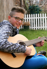 Young man playing on acoustic guitar