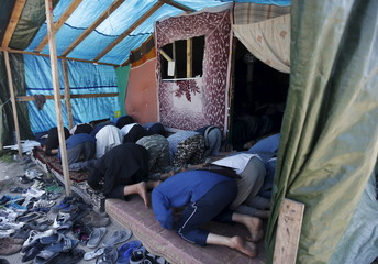 """Migrants pray at a makeshift mosque in """"The New Jungle"""" camp in Calais"""
