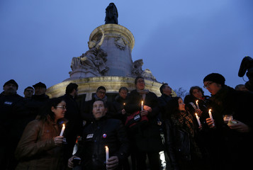 "People wearing stickers which read ""I am Charlie"" hold candles to pay tribute during a gathering at the Place de la Republique in Paris"