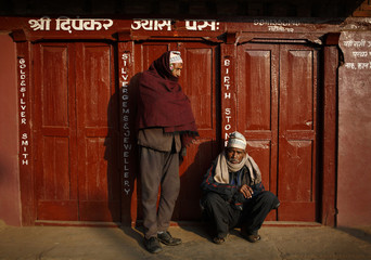 Men bask in the sun outside a closed shop at the ancient city of Bhaktapur