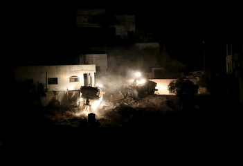 Israeli army bulldozers demolish a Palestinian house during an Israeli raid in the West Bank city of Jenin