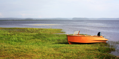 Orange boat at the lakeshore. Russian North. Tonde photo. Wide format. Sunny summer day. Kenozersky National Park, Arkhangelsk region.