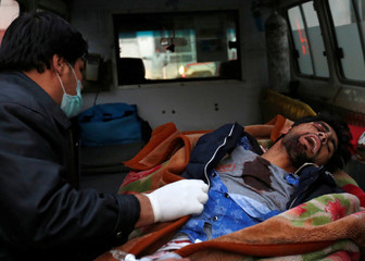 An Afghan man sits next to an injured person inside an ambulance after a suicide attack in Kabul, Afghanistan