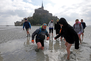 Sebastien Daligault, a guide at the Bay Saint-Michel, stands knee-deep in quicksand as tourists watch nearby during a walking tour at low tide around the 11th century abbey off France's Normandy coast