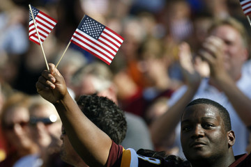A Washington Redskins' fan waves two U.S. flags before the Washington Redskins versus New York Giants NFL football game in in Maryland