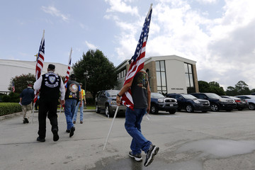 Mourners holding American Flags make their way to funeral services for Baton Rouge Sheriff's Deputy Brad Garafola at Istrouma Baptist Church in Baton Rouge,