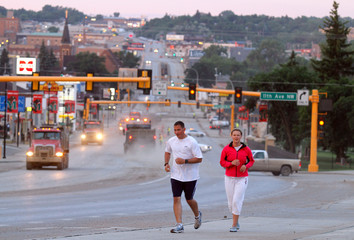 Joggers run along Broadway with the closed down Broadway Bridge in the background, as flood water spills over levees and dikes flooding sections of Minot