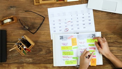 Fototapete - Businessperson Planning Schedule In Diary On Desk