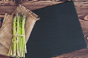 Bunch of fresh green asparagus spears on black stone on a rustic wooden table