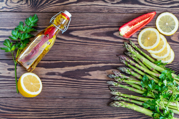 Bottle of olive oil with spices, bunch of fresh green asparagus spears and lemon on a rustic wooden table