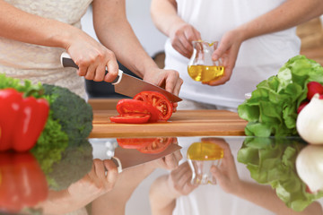 Closeup of two women are cooking in a kitchen. Friends having fun while preparing fresh salad