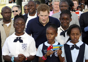 Britain's Prince Harry stands next to children during a tour of Harbour Island in Nassau