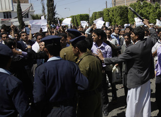 Police officers and a government backer with a baton block anti-government demonstrators during a rally in Sanaa
