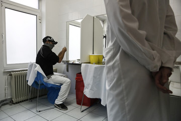 A paramedic watches a drug user as he prepares himself for an injection with a narcotic drug inside a supervised injection hall in Athens