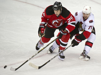 New Jersey Devils Cam Janssen and Ottawa Senators Nick Foligno chase puck in NHL game in Newark