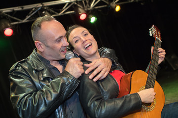 Couple in embrace while singing on stage