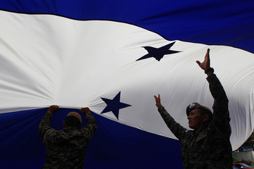 Military personnel stand underneath an Honduran flag while changing it at the presidential house in Tegucigalpa, Honduras