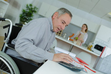 Man in wheelchair doing office work at home