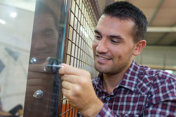 carpenter installing new door knob with lock