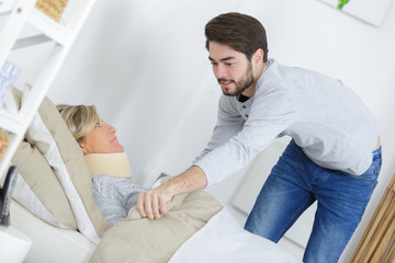 Young man pulling blanket around lady wearing neck brace