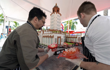 Pastry chefs Kraus and Green place flowers made from sugar on the birthday cake replica of the Beverly Hills city hall tower and Rodeo Drive in celebration of the 100th anniversary of the City of Beverly Hills