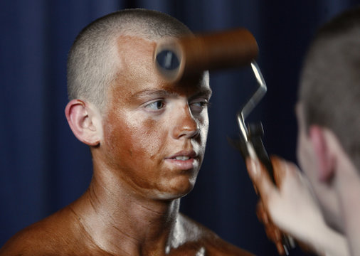 Participant has tanning lotion applied on his body during regional bodybuilding and fitness competition in Minsk