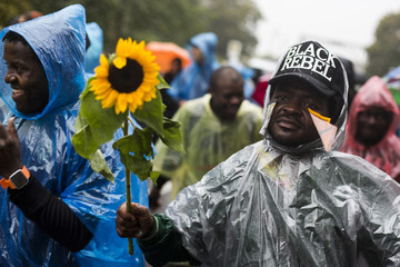 Refugee holds sunflower as he cross Glienicke Bridge from Potsdam into Berlin  during protest march