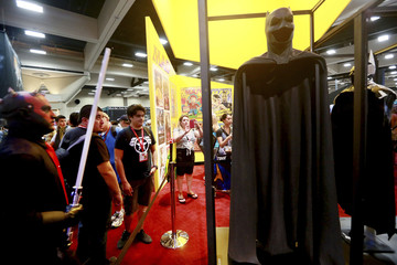 Attendees look over the new Batman outfit on at the comic franchise's 75th anniversary display during the 2014 Comic-Con International Convention in San Diego, California