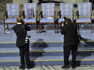 Photographers take pictures of the empty chairt with diploma and medal of Nobel Peace Prize winner Liu Xiaobo during the Nobel Peace Prize ceremony in Oslo