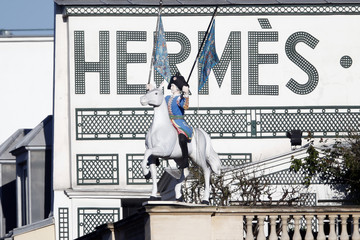 A view shows a horse rider waving two Hermes scarves in front of the logo of French luxury group Hermes on the group's headquarters building roof in Paris