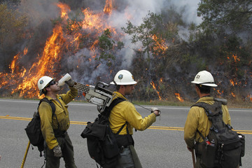 Firefighter Tyson Navarro and his colleagues watch a burn out operation along Highway 1 in Big Sur, California