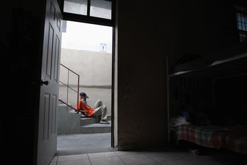 """Migrant from Central America rests at the stairs of  """"Posada Belen"""" migrant shelter in Saltillo"""