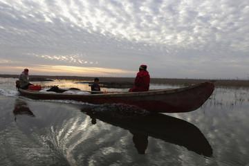 A family boats through the Chebayesh marsh in Nassiriya