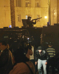 A riot police officer stands in a vehicle as teargas is used to disperse demonstrators in downtown Cairo