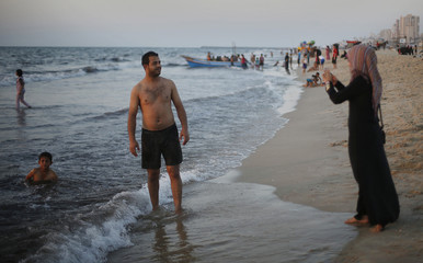 A Palestinian woman takes a photograph of her husband on a mobile phone at the beach in Gaza City