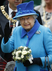 Britain's Queen Elizabeth waves as she arrives at Edinburgh Waverley Station before boarding a train drawn by a steam locomotive to travel along the Scottish Borders Railway in Scotland