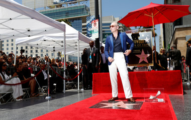 Recording artist Pitbull poses on his star after it was unveiled on the Hollywood Walk of Fame in Los Angeles
