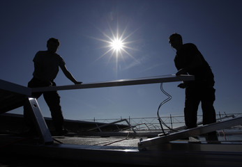 A worker installs solar panels on the roof of the Palexpo Exhibition Center in Geneva