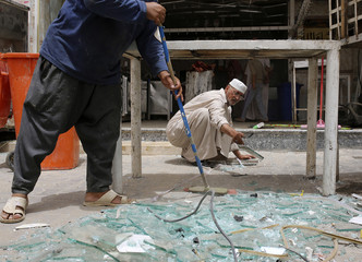 Civilians clear shattered glass at the site of a car bomb attack in Najaf