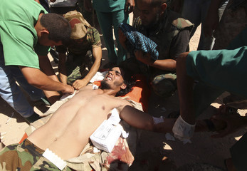 A member of the anti-Gaddafi forces receives medical attention in Om El Khanfousa
