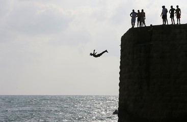 A man jumps into the Mediterranean Sea in the northern Israeli city of Acre