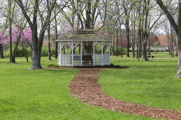 The white gazebo under the trees in the park.
