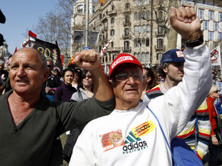 Protesters hold placards and flags during a demonstration against a labour reform imposed by the Spanish government in central Barcelona