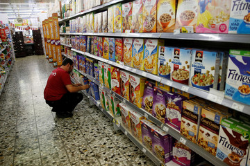 An employee arranges cereal boxes for sale at a supermarket in Jerusalem